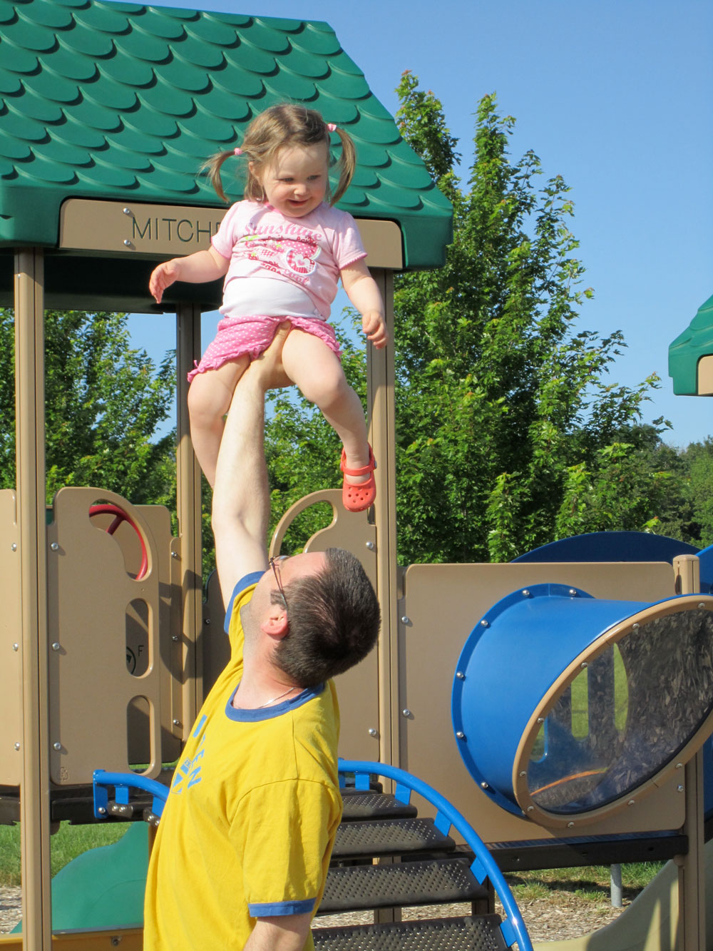 Richie lifting Gigi high up in the air at the playground.