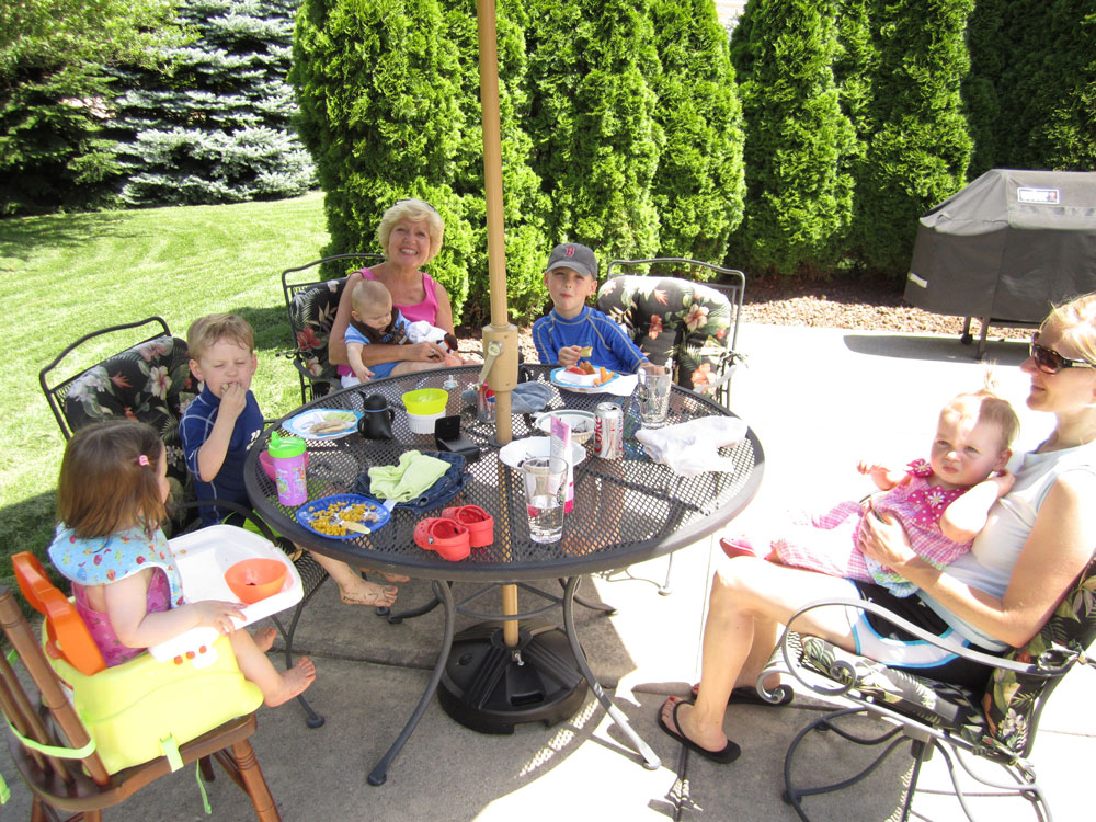 Linda and grandkids eating lunch together poolside.