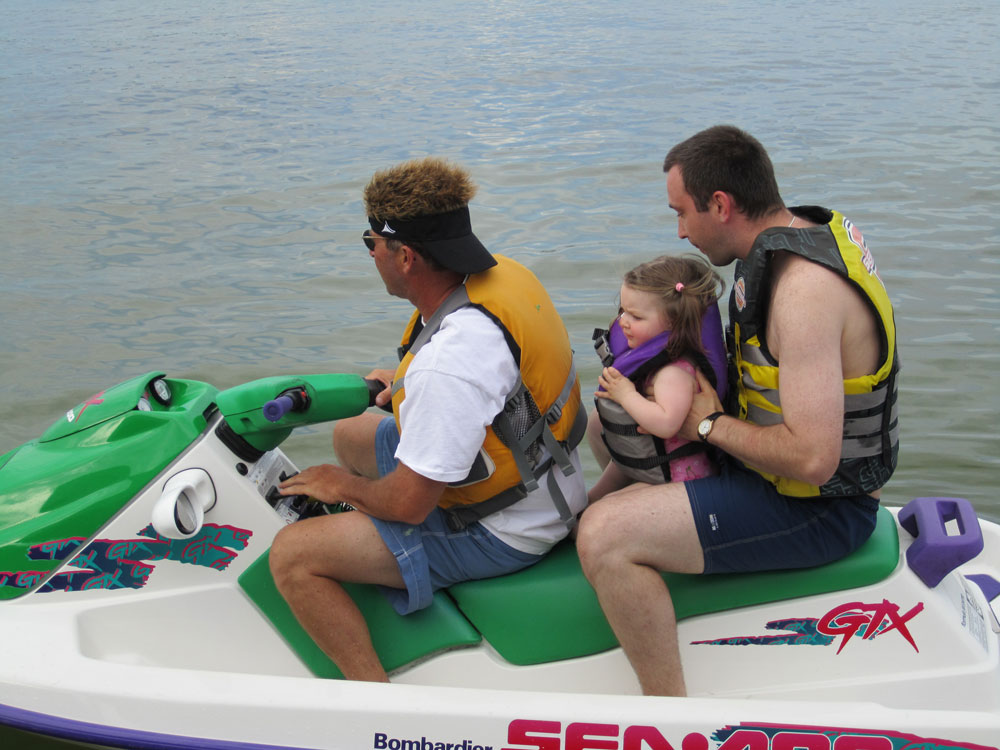 Gigi on a jet ski nestled in her dad's lap.