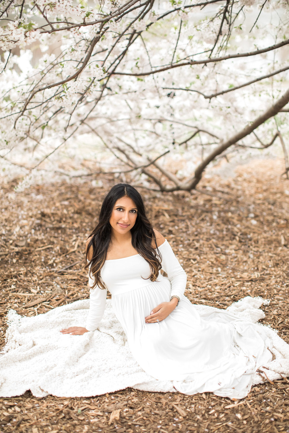 Maternity portraits in Central Park NYC among the cherry blossoms of beautiful Indian mama