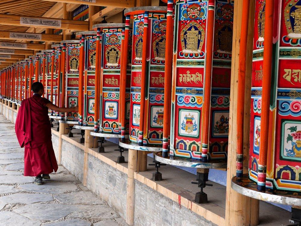 A monk turning prayer wheels along the 3.5km Kora