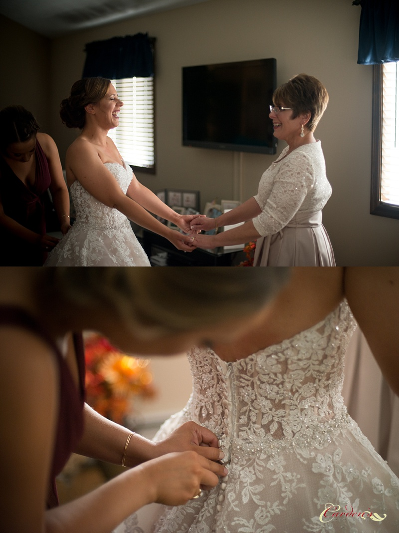 Ashley and her Mom holding hands as Ashley is buttoned into her wedding dress.