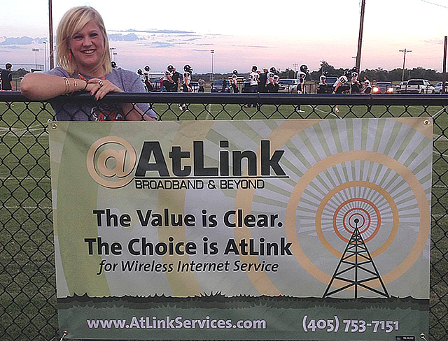 Girl standing by AtLink banner at a football game in rural Oklahoma