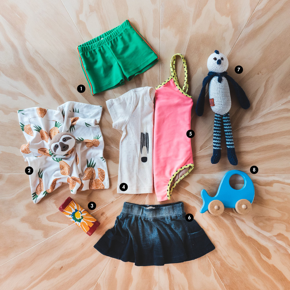 1. Shorts de banho da Amapô Jeans Kids; 2. Naninha da Timirim Brasil; 3. Chocalho da Brasil no Fio; 4. Camiseta da Nó&Nó; 5. Maiô da Amapô Jeans Kids; 6. Saia da Nó&Nó; 7. Boneco da Lolo Fofuras; 8. Brinquedo da Calu Rosa