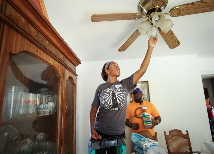 Students and local volunteers install efficient lightbulbs to reduce electricity consumption.
