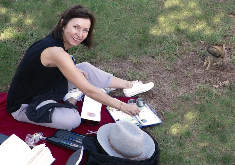 Miniaturist Amanda Em painting plein air for My Small paintings watched by a curious squirrel