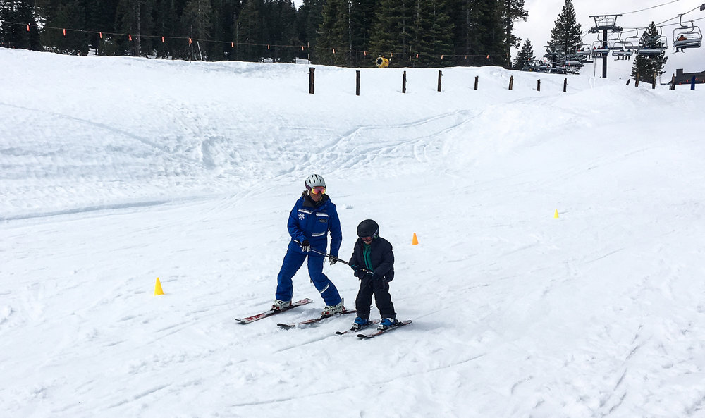 Our instructor demonstrating her skill and patience while helping my younger son feel comfortable on skis for the first time