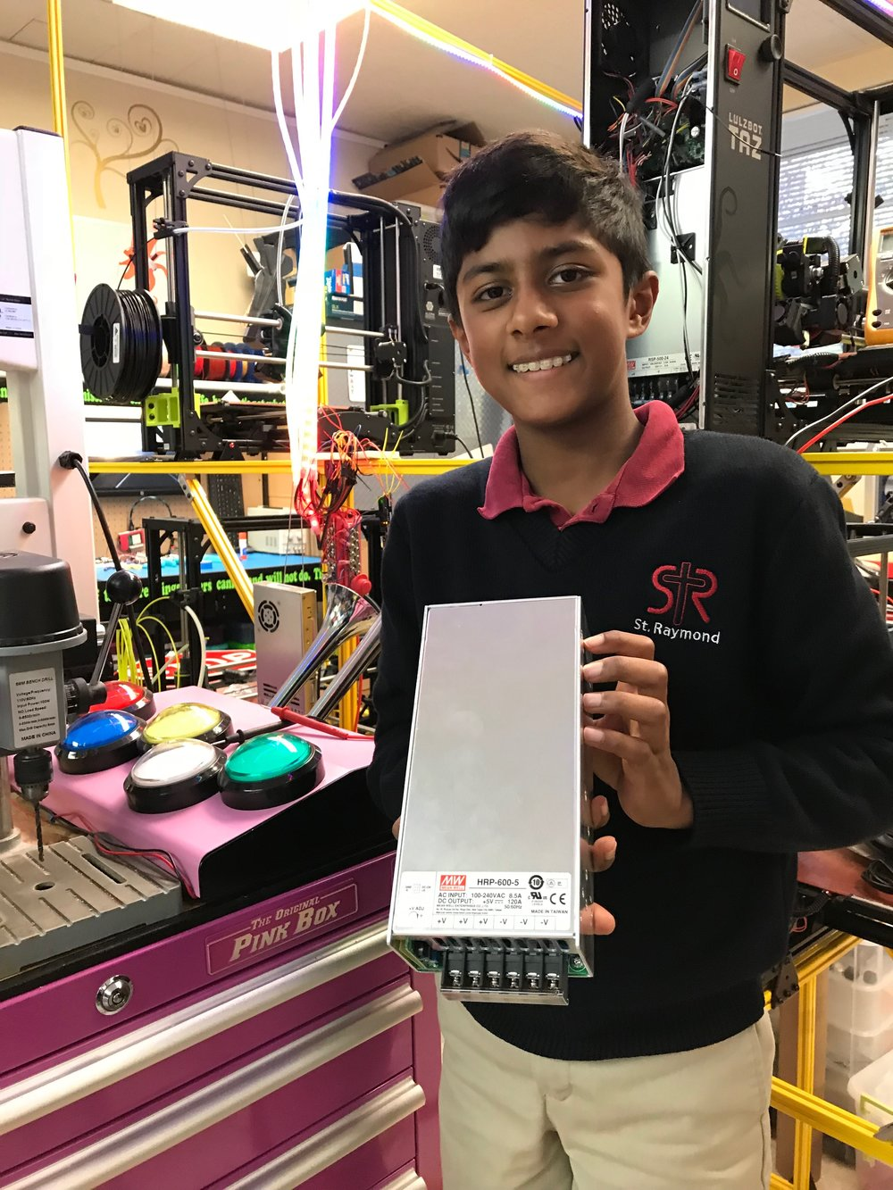 A proud 6th grade student holds up a Meanwell 60Amp power supply before installation in the St. Raymond Makerspace without adult help (but with adult supervision)