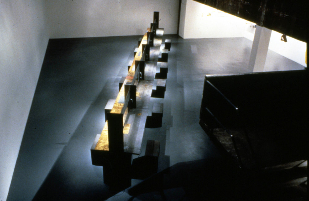 Table of Voices , 1996, lead, gold leaf, steel frames, glass, recorded voices on phones, 60 x 5 x 6' feet