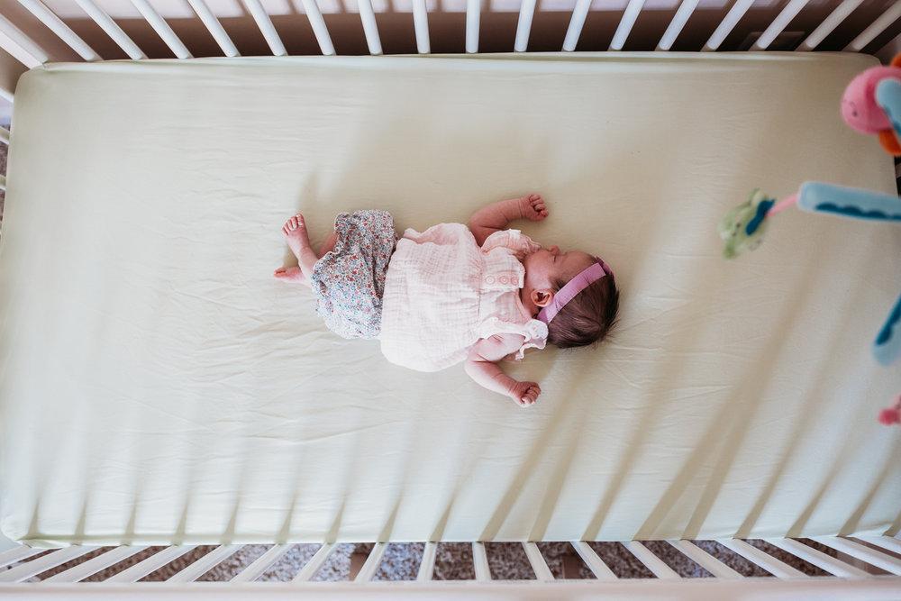 overhead view of newborn baby girl in crib