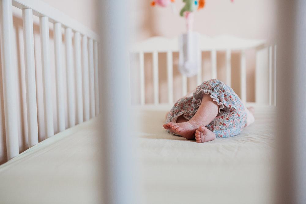 newborn baby girl feet in crib