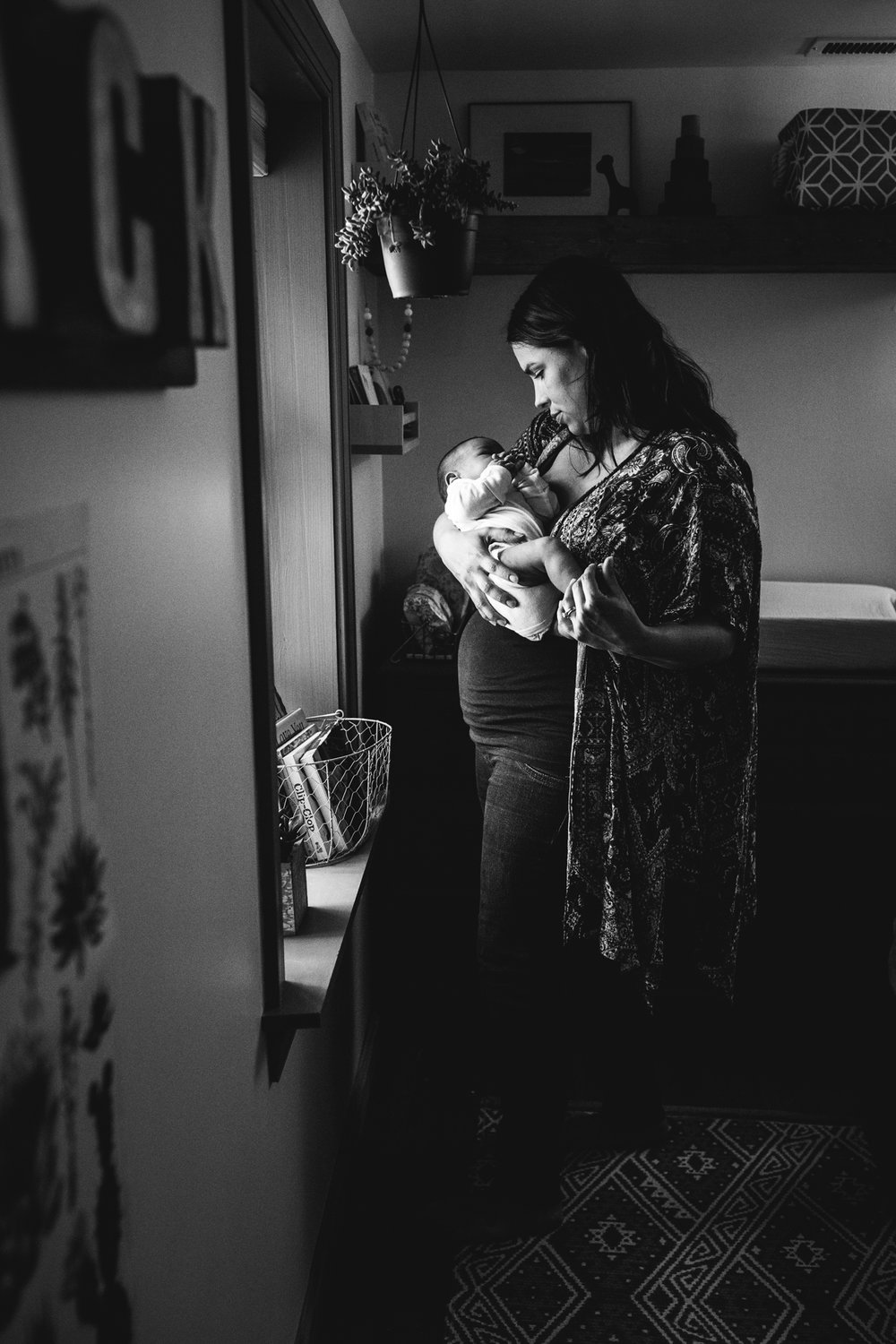 black and white mom holding baby boy in nursery