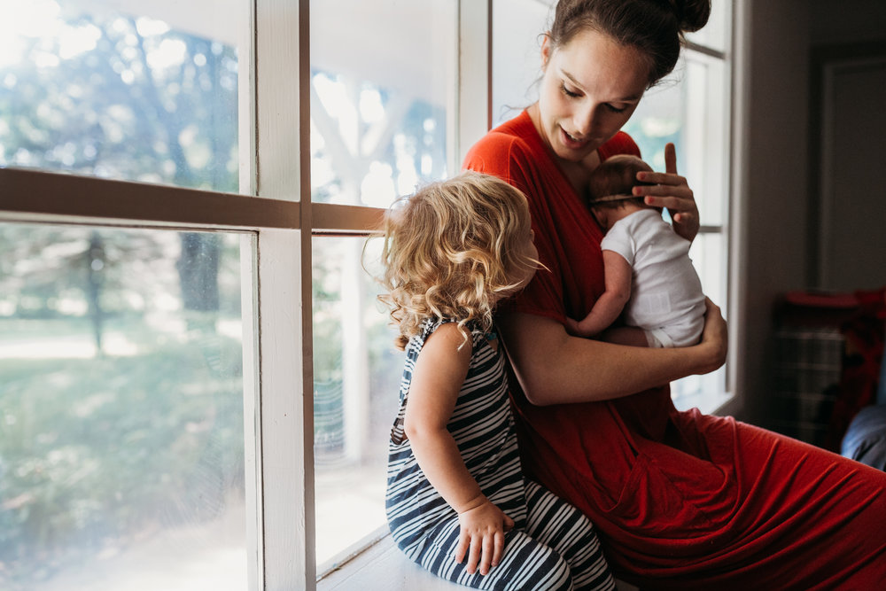mom sitting in window seat with toddler boy and newborn baby girl
