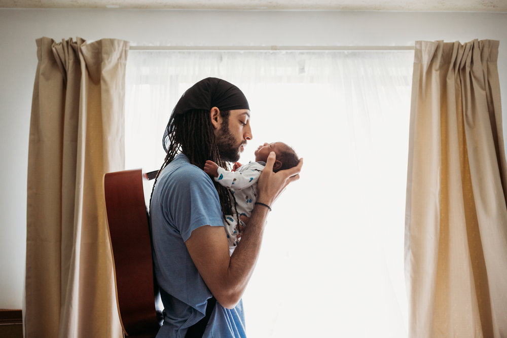 African American dad holding newborn baby boy and guitar