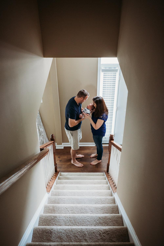 couple holding newborn baby boy in stairway