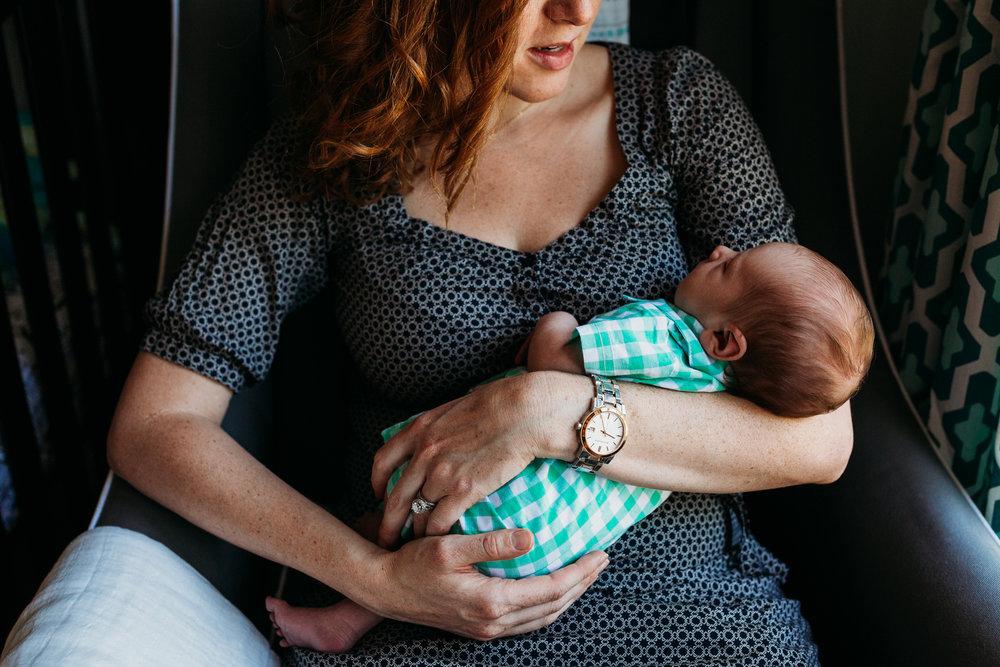 new mom holding newborn baby boy in chair