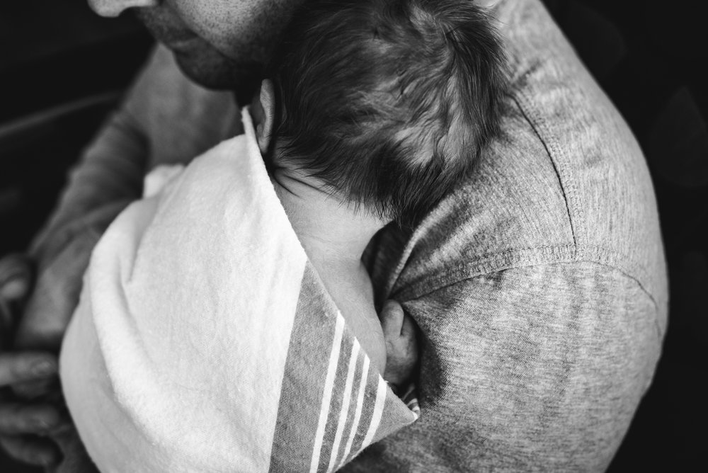 newborn baby boy snuggled on dad's shoulder