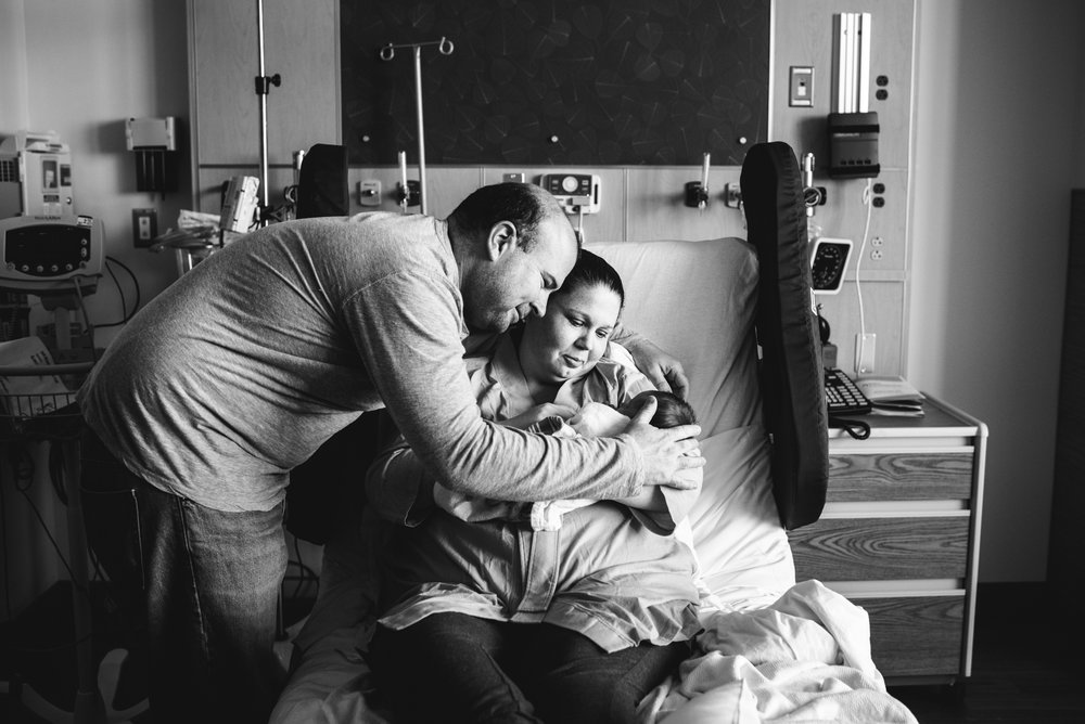 mom and dad look at newborn baby boy in hospital bed