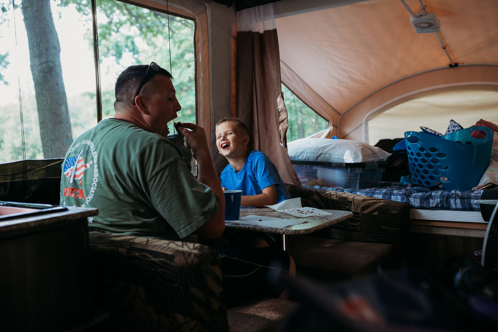 father and son laughing in camper