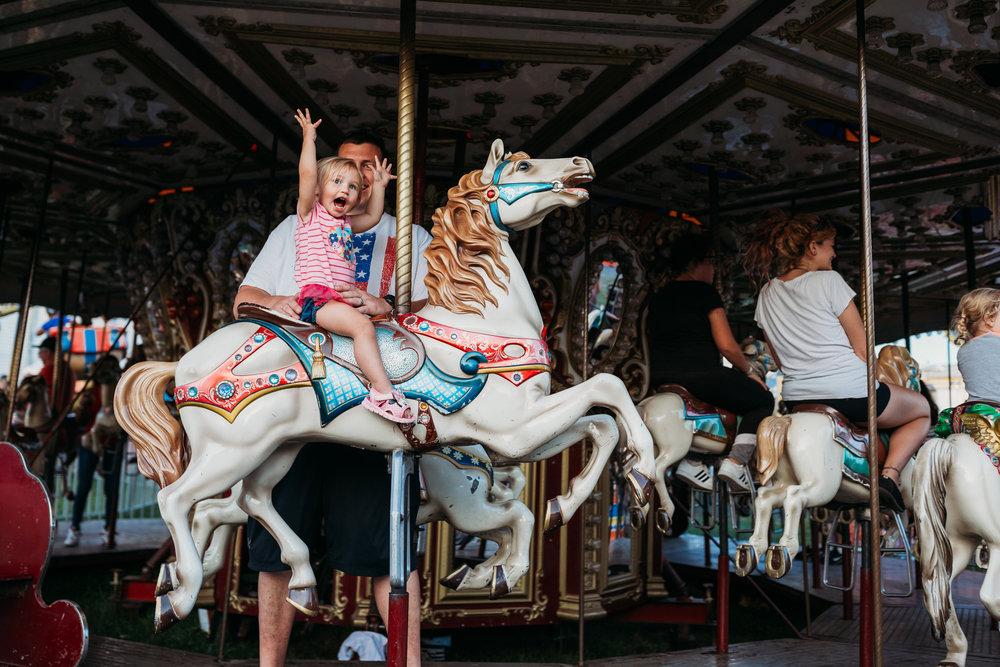 toddler girl smiling on carousel