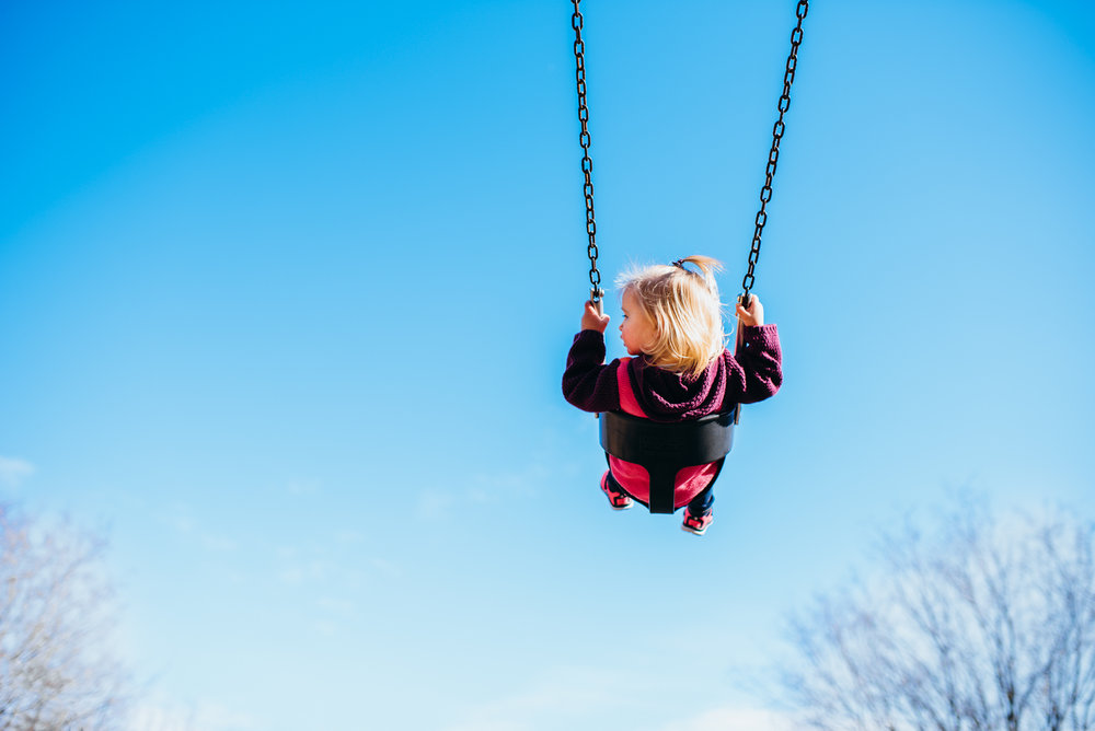 toddler girl swinging with big blue sky