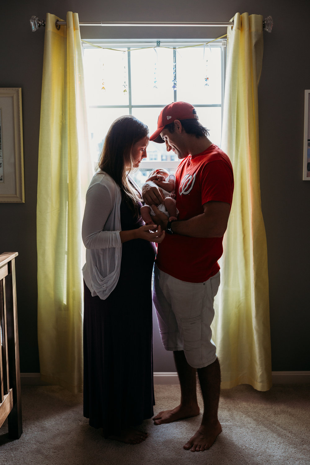 couple standing in front of a window holding newborn baby boy