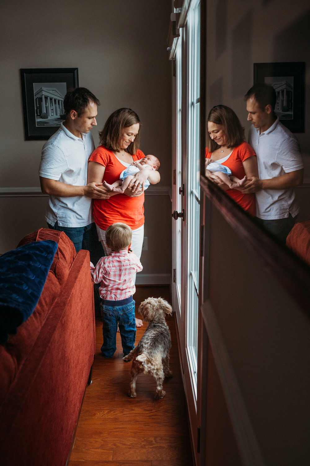 Couple with toddler boy and dog holding newborn baby girl