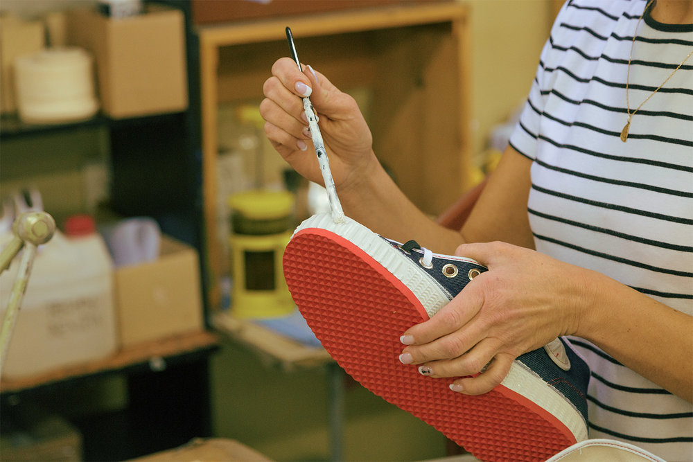 A co-worker finishing the rubber before the shoe has dried. The shoes are then packed for shipping.