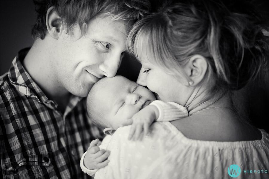 Portrettfotografering i Oslo av en familie på tre. Svarthvittbilde av mor, far og baby.