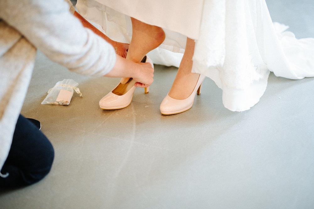 Bruden tar på skoene og brudekjolen i frisørsalongen