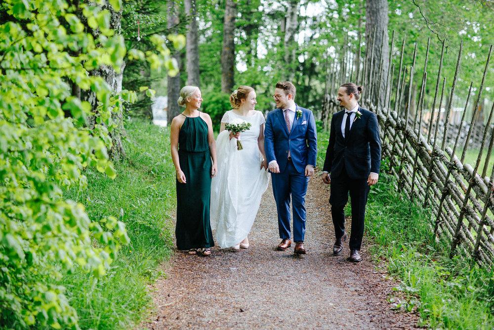 Brudepar går sammen med sine forlovere på en sti i skogen