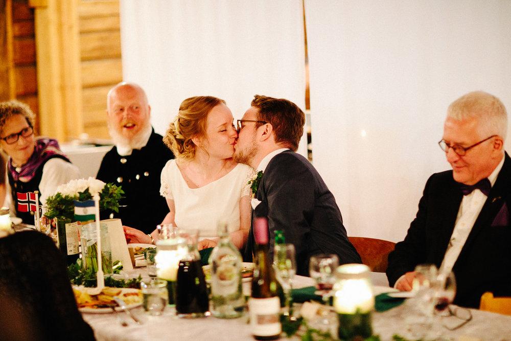 Brudepar kysser under middagen i bryllupet