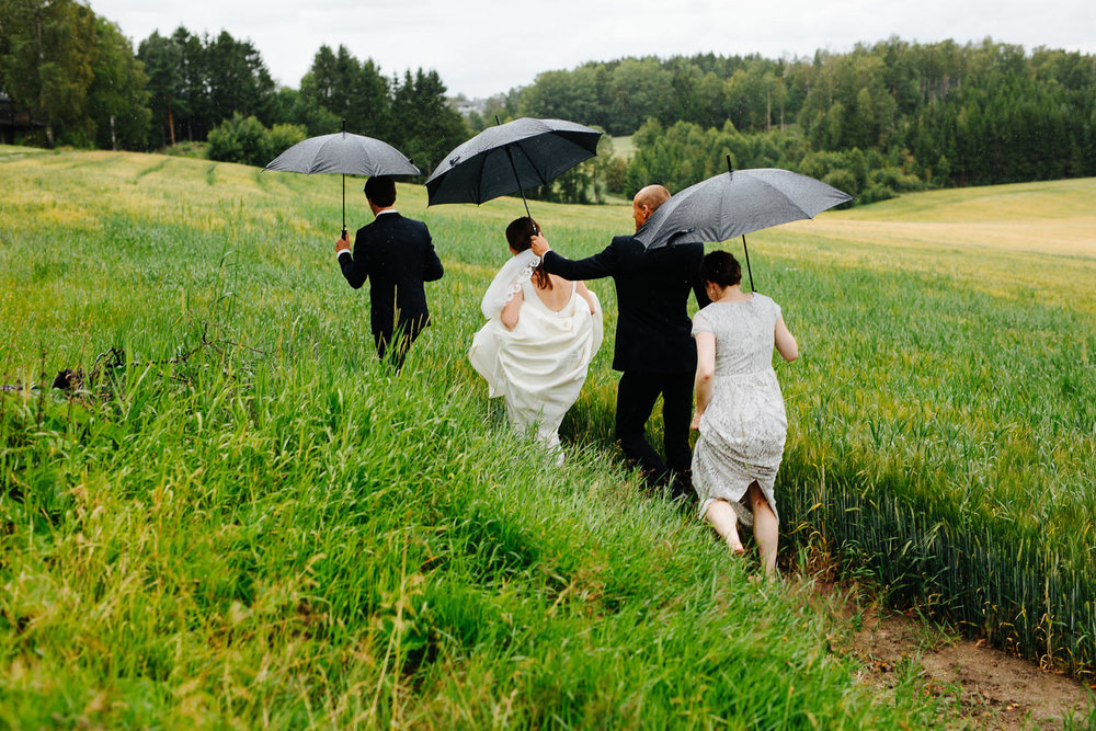 Brudepar og forlovere i regnvær med paraplyer i åkeren