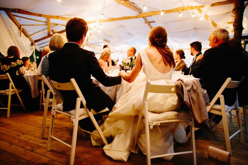 Brudepar holder hender under bryllupsmiddagen