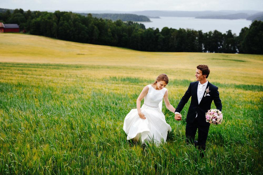 Brudepar i åkeren, et bryllupsbilde i Sarpsborg med utsikt mot Isesjøen.