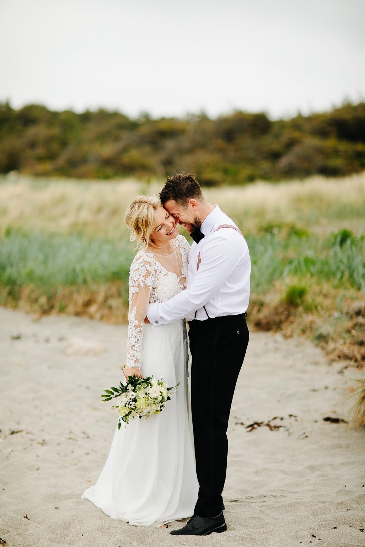 Bryllupsbilde av brudepar på stranden på Hvaler i Østfold.