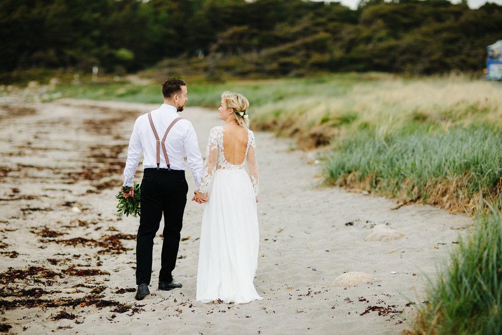 Brudepar går bortover stranden på Hvaler.