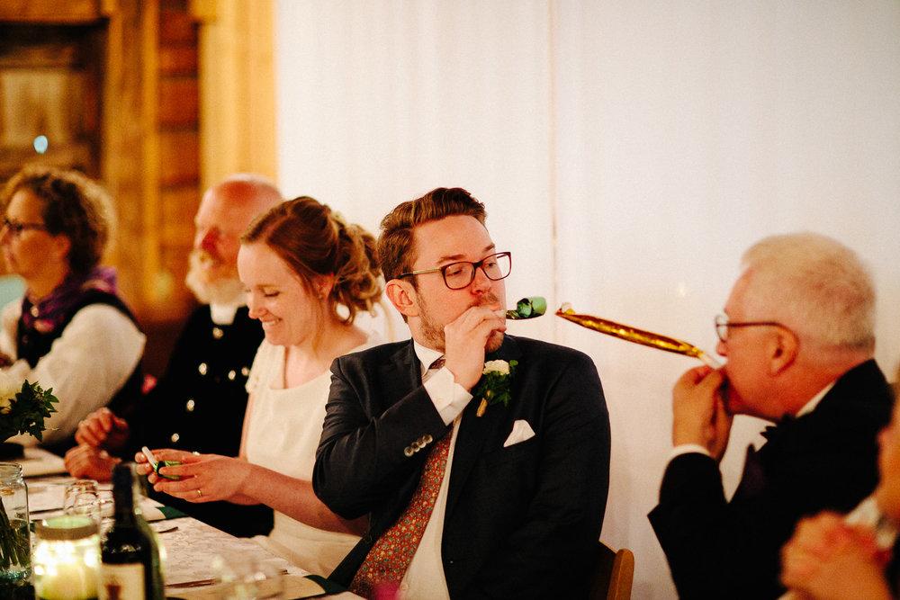 Brudgom og brudgommens far blåser fløyte under bryllupsmiddagen.