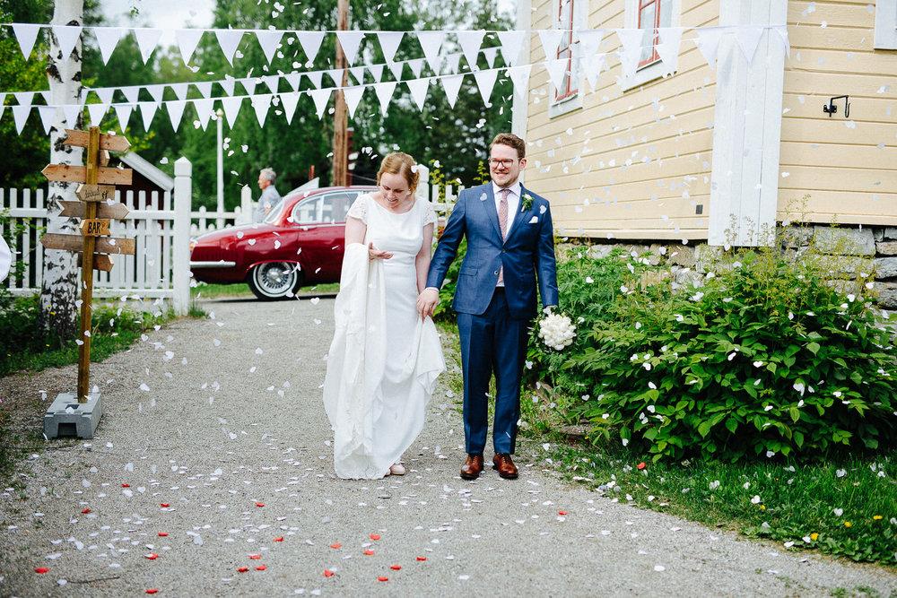 Brudepar ankommer festen i en rød bil under et bryllup i Sverige.