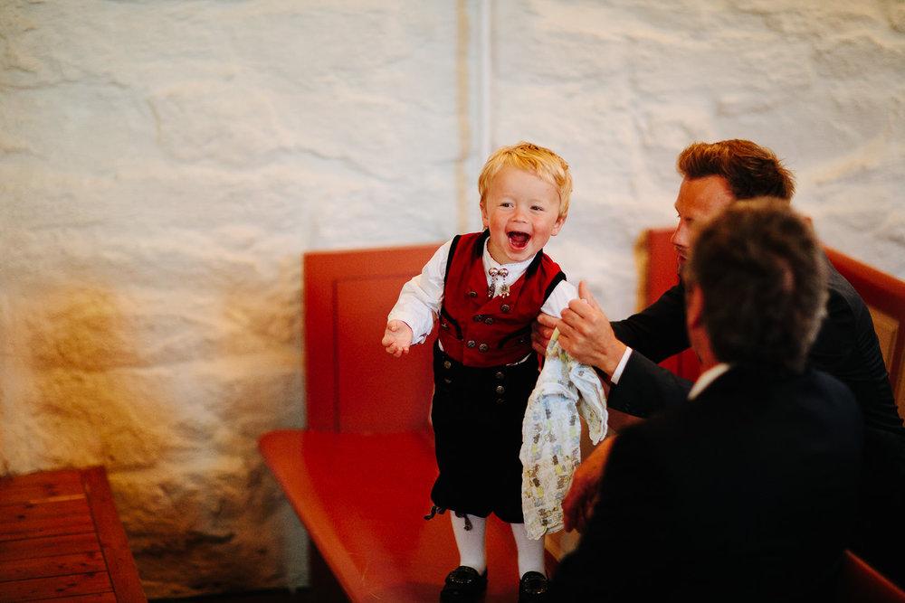 Liten gutt med bunad under vielse i et bryllup i kirken.