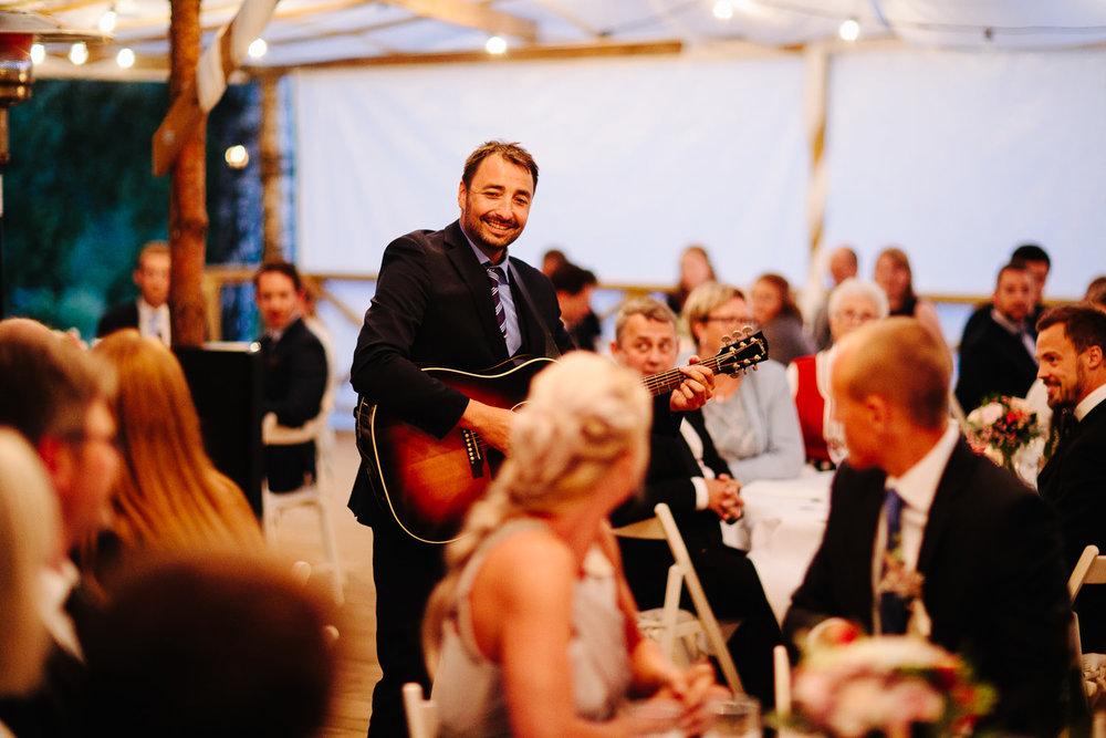 Trubadur med gitar spiller under bryllupsmiddagen.