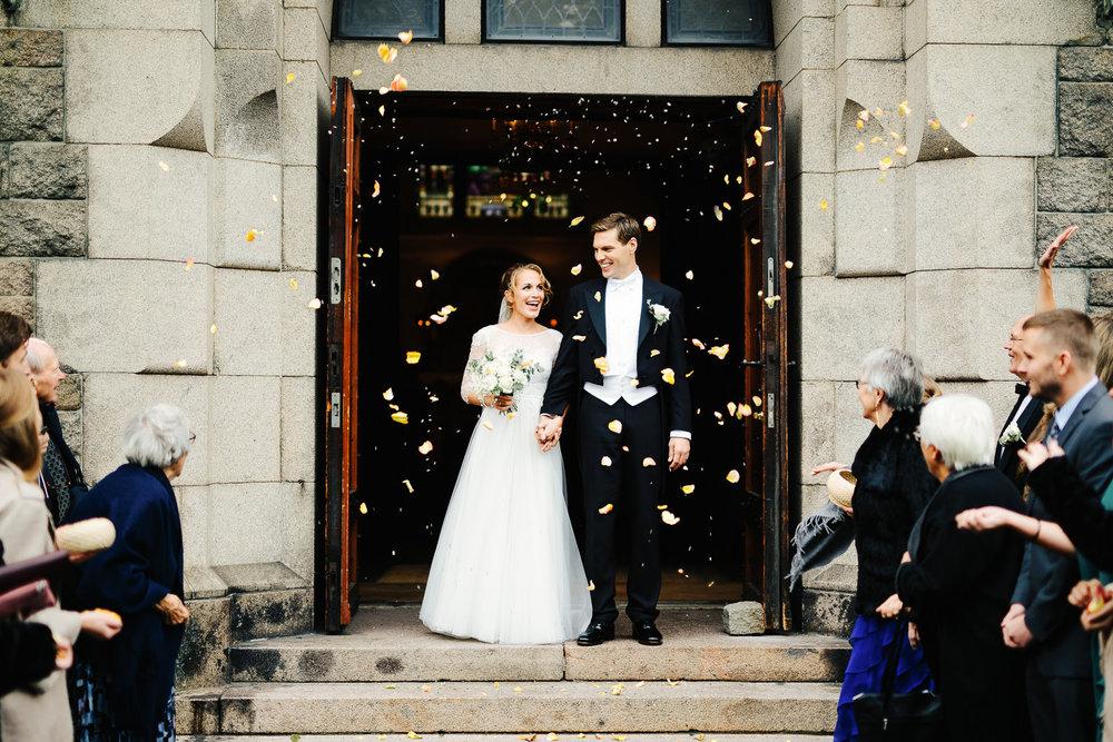 Bryllupsgjestene kaster roseblader på brudeparet etter vielsen i Fagerborg kirke i Oslo