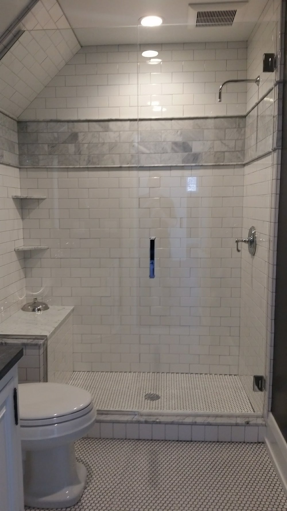Full tile shower w/ bench and Euro glass door.