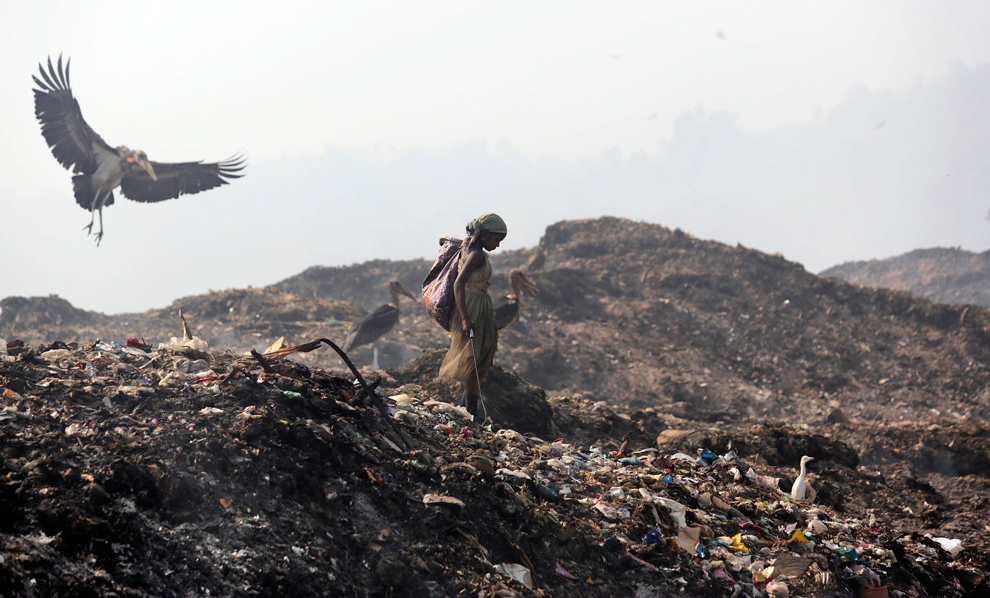 A woman looks for recyclable items at a landfill on the outskirts of Guwahati Image: Flickr CC/  Jordi Bernabeu Farrús