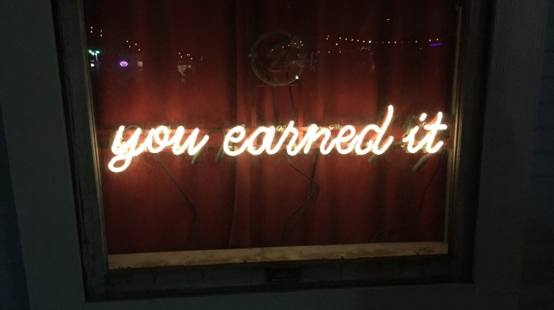 "A window at Half-Step is illuminated by the bar's mantra of ""you earned it."""
