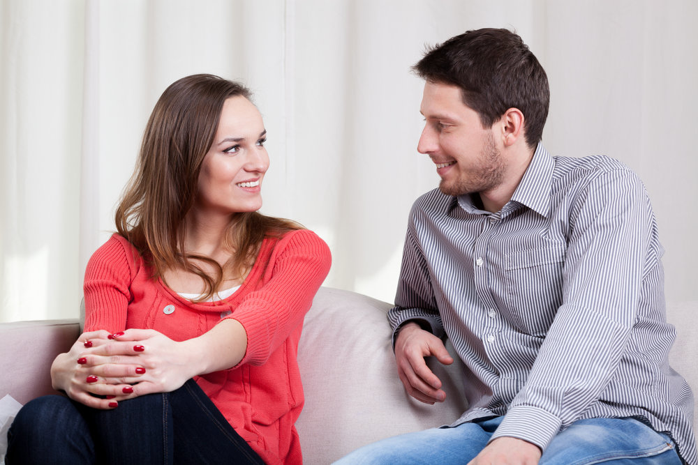 View of loving couple sitting on couch