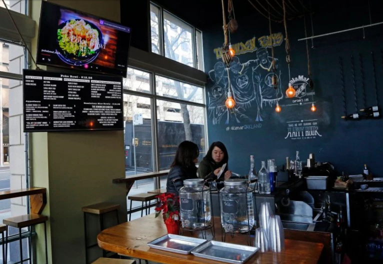 Customers decide to sit at the bar with their food during a soft opening after a re-structuring of AlaMar restaurant on Friday, Jan. 6, 2017 in Oakland, Calif. Nelson German, owner of AlaMar restaurant, decided to change his restaurant from a table-service model to a new fast-casual model in an effort to address the financial pressures he and other restaurant owners are up against. (Laura A. Oda/Bay Area News Group)