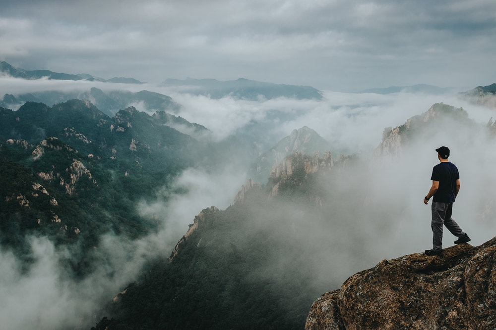 A solo hiker exploring the mountains of Seoraksan in South Korea. A beautiful foggy day made for this dynamic photo.