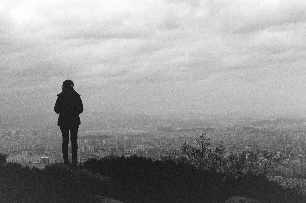 A young girl looks out over the city from this high vantage point in South Korea. This picture was captured with an old analog film camera.