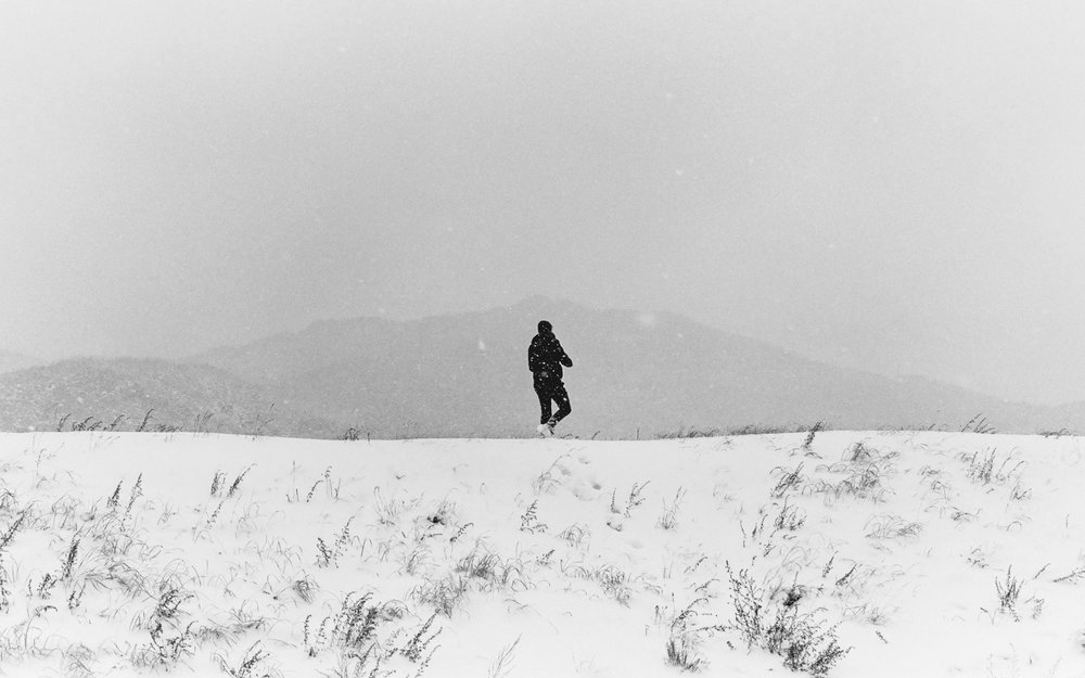 A solo hiker hikes along this embankment during a snowy day in January.  Shot on Kodak BW film in South Korea.
